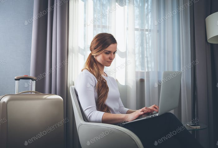 Pretty woman in modern hotel room sitting on armchair and using laptop