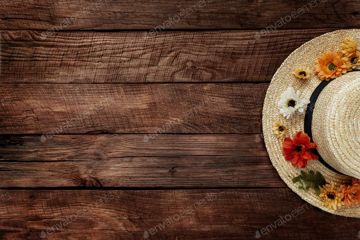 Autumn, autumntime concept, brown wooden background, straw hat and flower heads