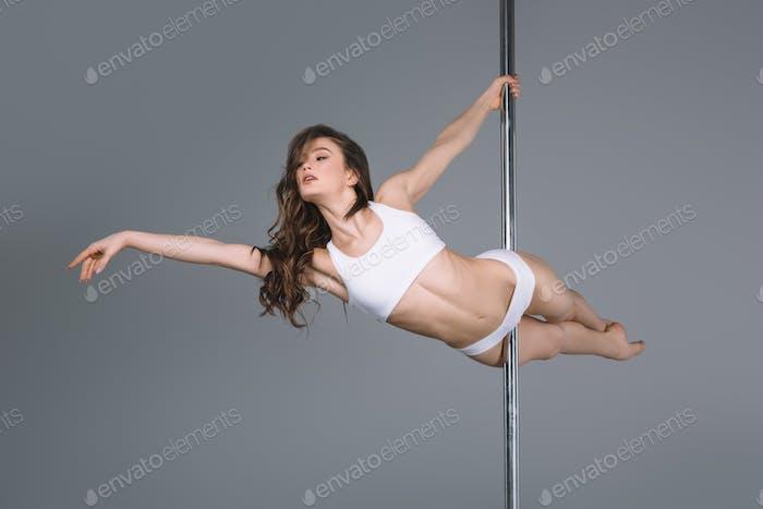 beautiful young woman in sportswear dancing with pole on grey