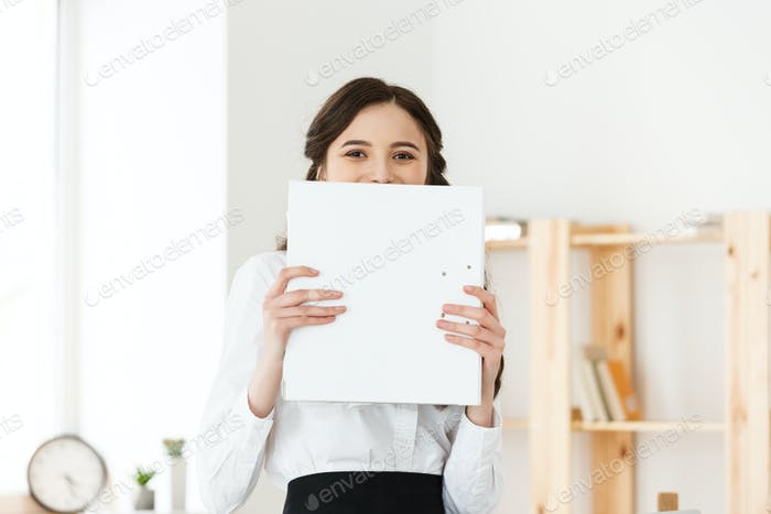 Young woman with surprised eyes peeking out from behind paper poster. Businesswoman holding big