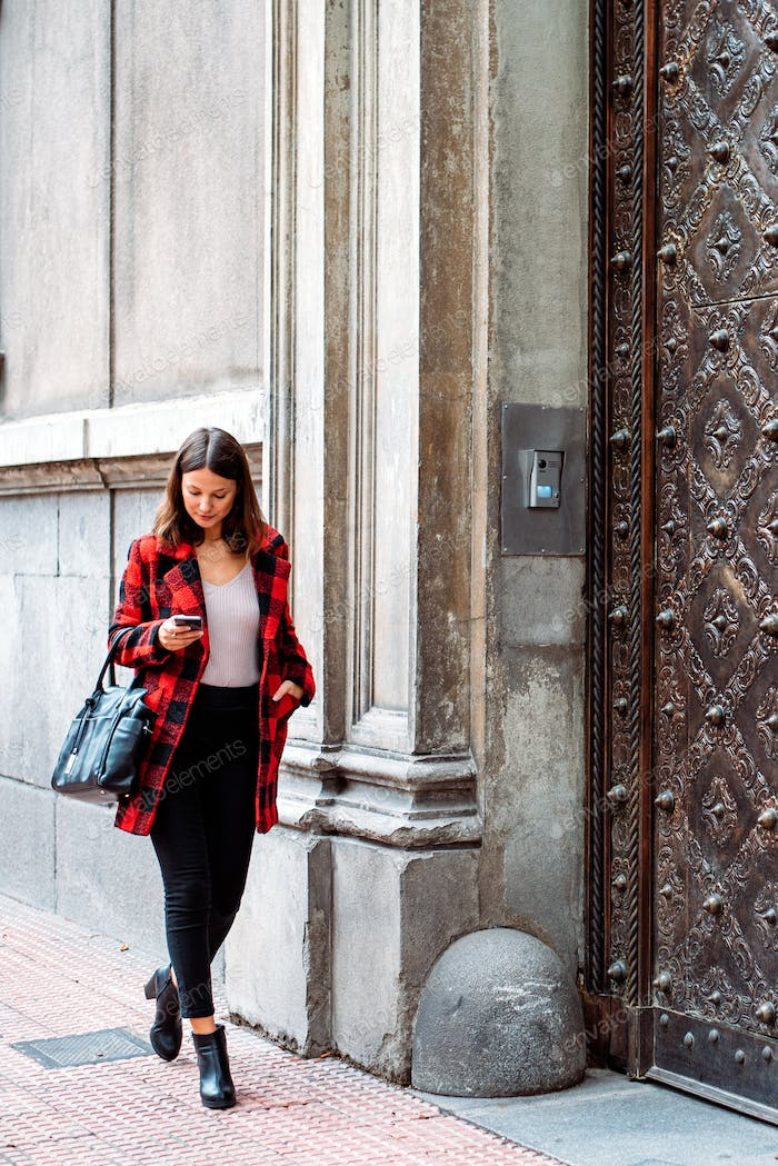 pretty young woman walking on the street using smartphone