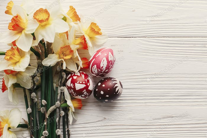 stylish colorful easter eggs with spring flowers daffodils on rustic white wooden background