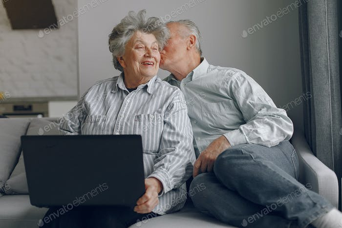 Elegant old couple sitting at home and using a laptop