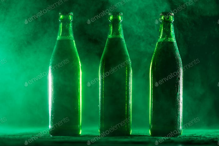 Drei grüne Bierflaschen auf staubigem Hintergrund.