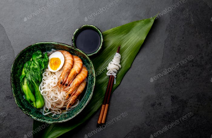 Rice noodles with Shrimps, Egg, Pok choy cabbage in green bowl, gray background. Top view