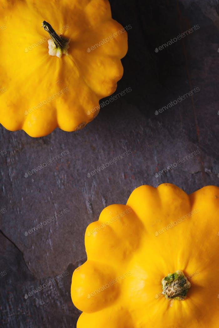 Yellow fresh squash patty pan on the dark stone background vertical