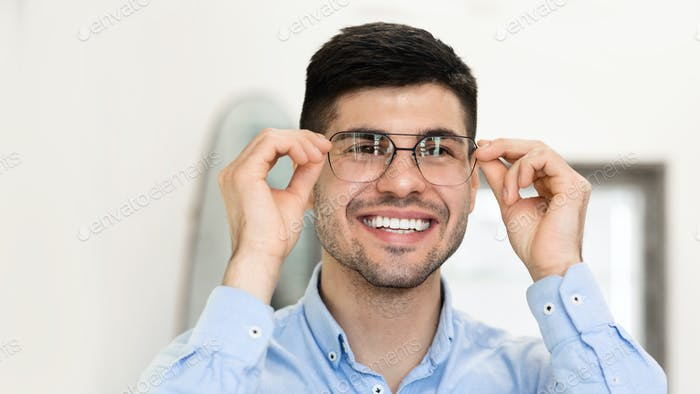 Portrait of smiling handsome man trying on spectacles