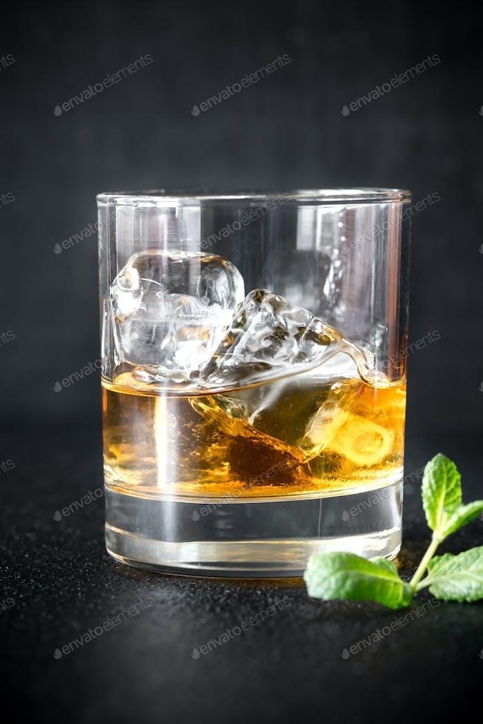 Glass of rum on the dark background