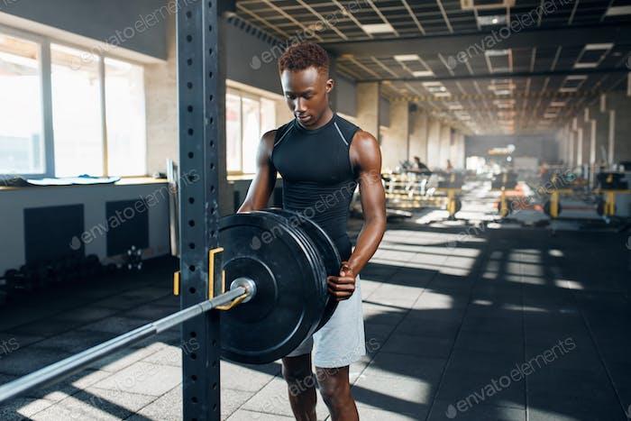 Muscular man in sportswear prepares barbell in gym