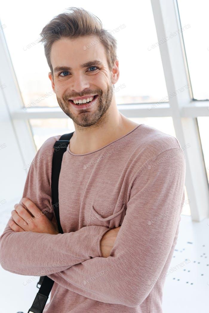 Bild des jungen Mannes lächelnd, während er über helles Fenster in Innenräumen steht