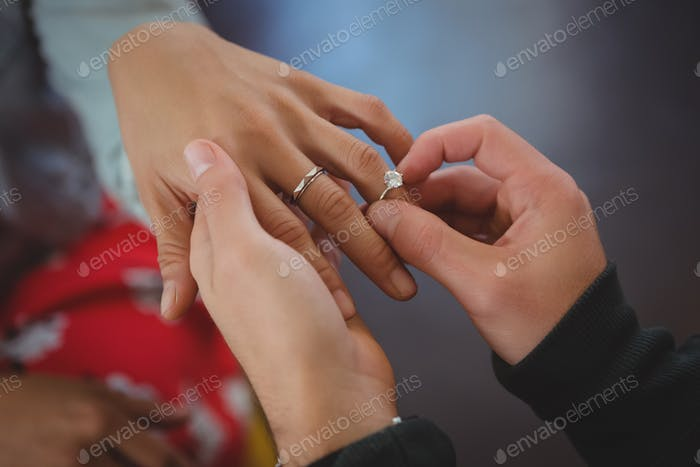 Cropped hand of man putting ring on woman finger