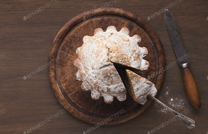 Top view on fruitcake on rustic wooden background