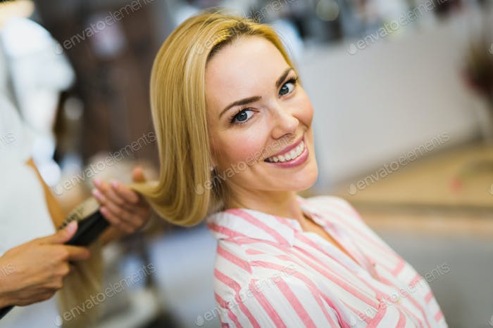 Happy young beautiful woman at the hair salon