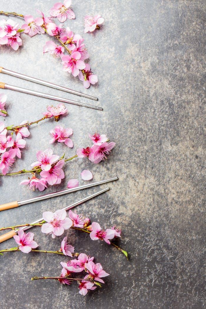 Essstäbchen und Sakura-Zweige auf grauem Steinhintergrund. Japanisches Lebensmittelkonzept. Draufsicht, Kopierraum
