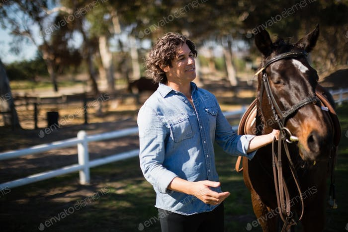 Man standing with horse in the ranch