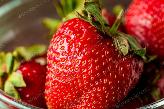 Fresh appetizing red ripe strawberries picked up in the garden into glass bowl