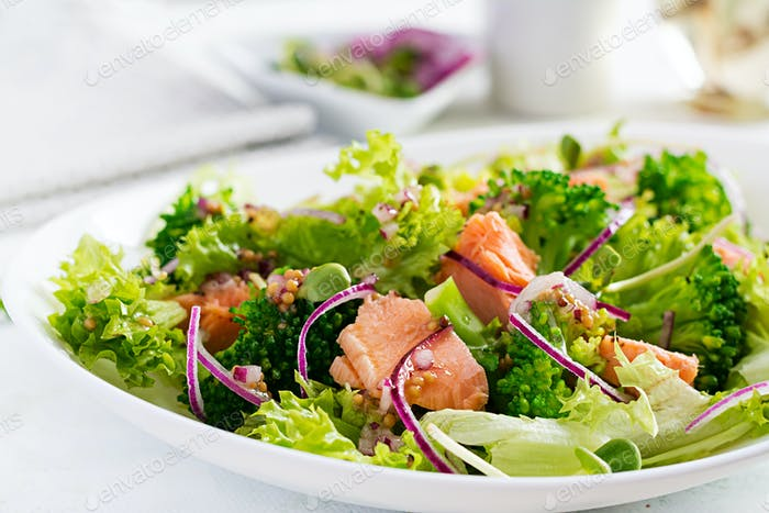 Salad of baked fish salmon, broccoli, lettuce, red onion and dressing. Fish menu. Seafood - salmon.