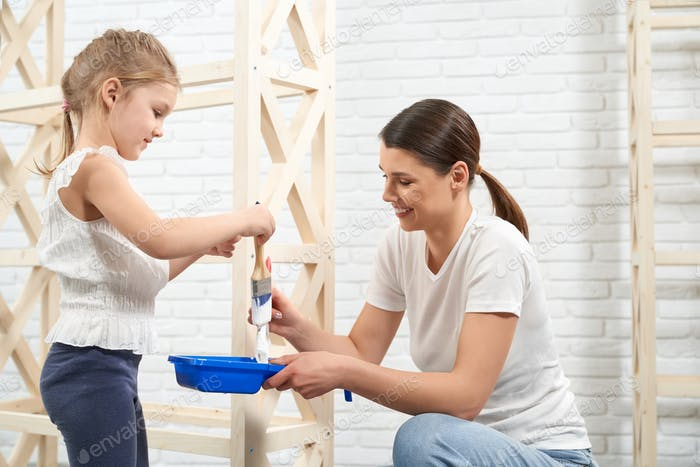 Smiling mother and daughter painting wooden rack