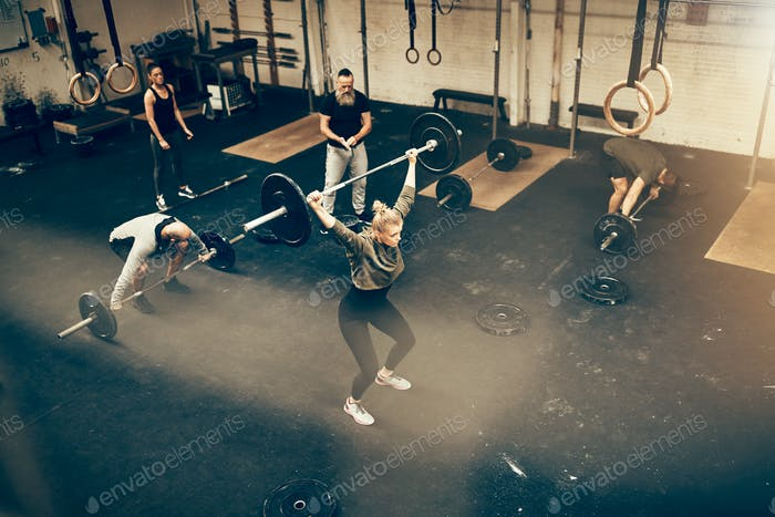 Fit people lifting weights while exercising together in a gym