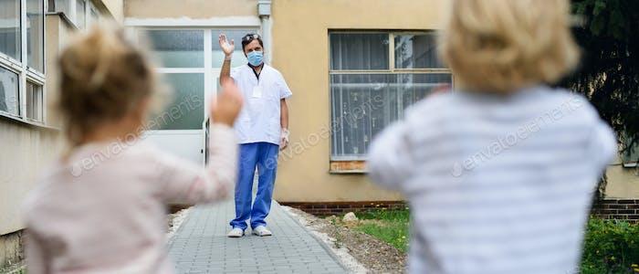 Kinder Gruß Vater Arzt aus der Ferne vor Krankenhaus, Coronavirus Konzept