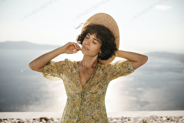 Close-up portrait of brunette curly lady sensitively smiles with closed eyes. Short-haired woman in