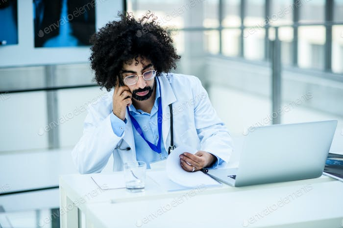Portrait of thoughtful male doctor in hospital, corona virus concept