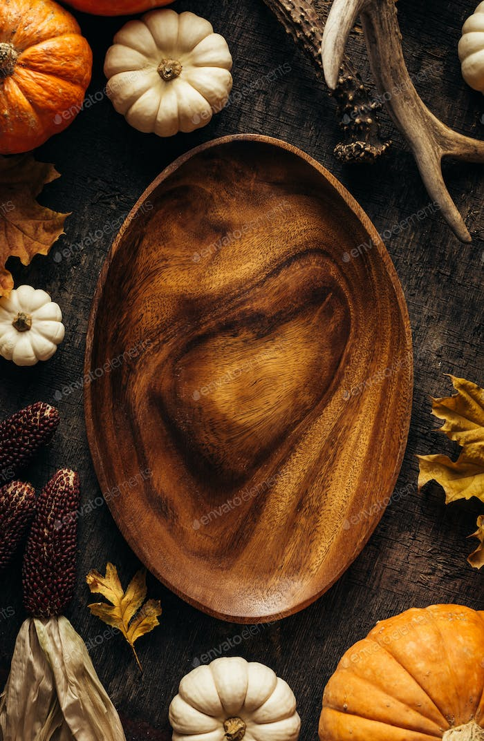 Empty wooden dish on a dark background with autumn decorations. Top view. Copy space