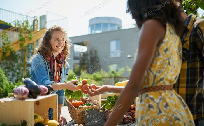 Friendly woman tending an organic vegetable stall at a farmer's market and selling fresh vegetables