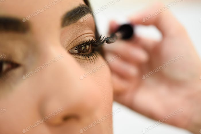 Make-up artist putting on the eyelashes of an African woman