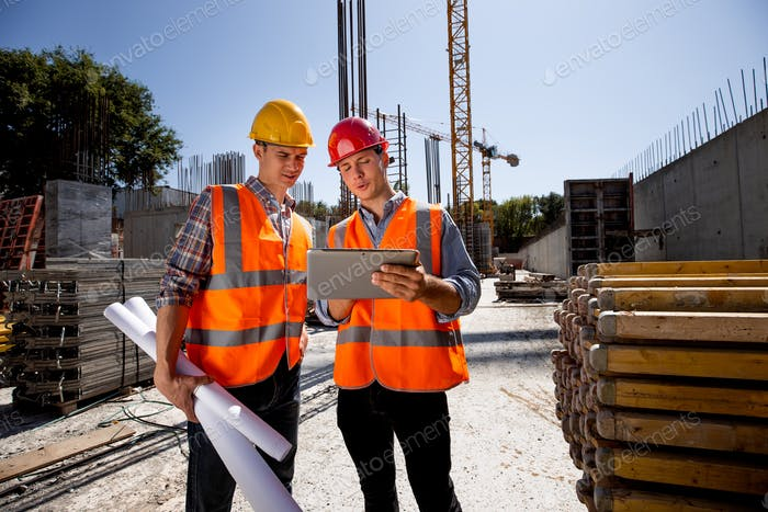 Architect and structural engineer dressed in orange work vests and helmets discuss a building