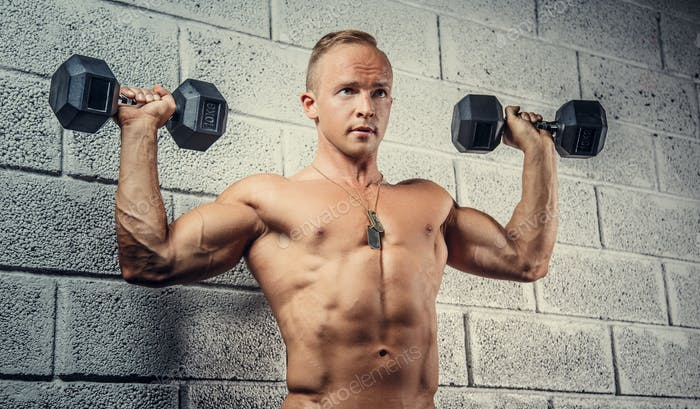 Young man doing exercises with dumbells.