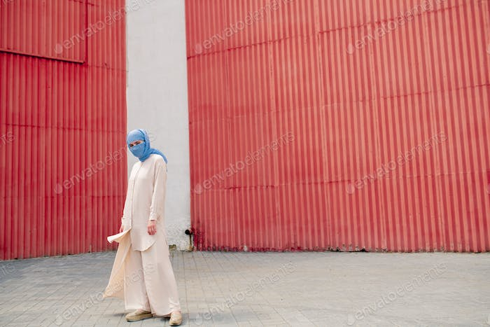 Young muslim female in blue hijab and casualwear on background of wall exterior