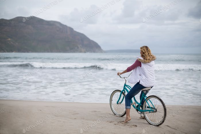 Mature woman riding bicycle on the beach