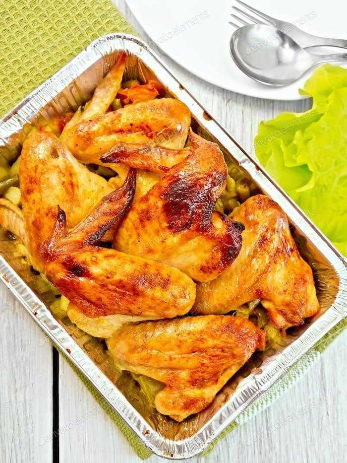 Hähnchenflügel mit Gemüse in Pfanne aus Folie gebraten