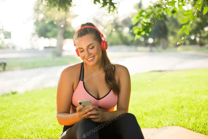Young beautiful smiling plus size woman in pink sporty top and l