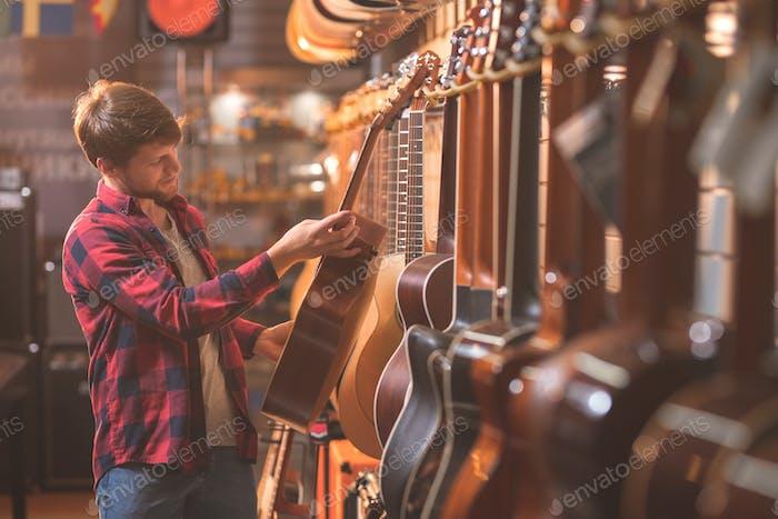 Ein junger Mann wählt eine Gitarre