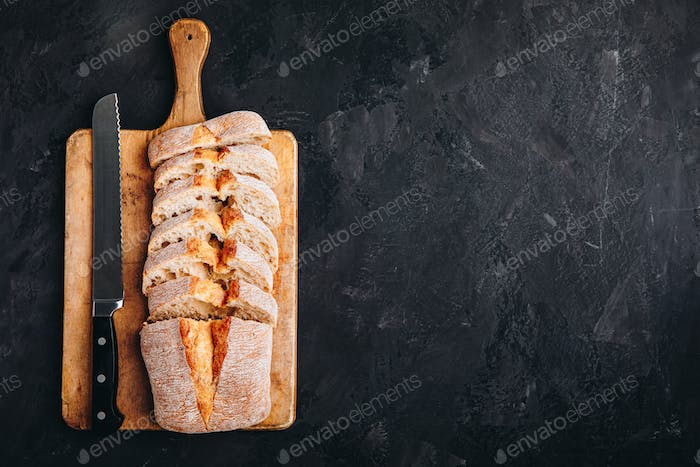 Italian ciabatta bread slices on wooden chopping board on dark stone concrete backdrop