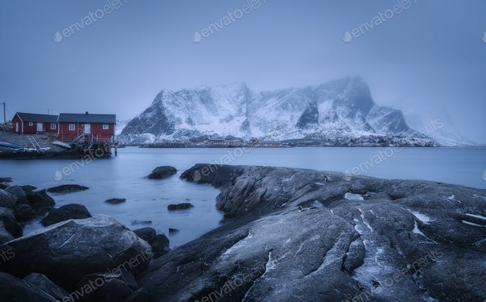 Beach with stones in blurred water, red rorbu and snowy mountain