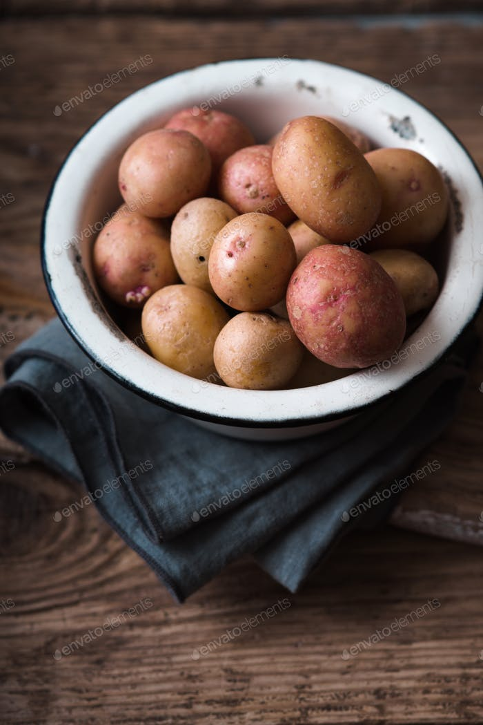 Raw potatoes red and white in bowl on a napkin