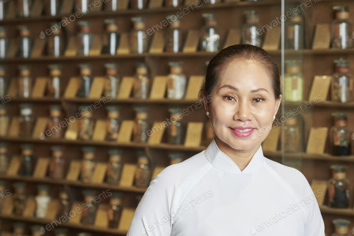 Woman working at old traditional pharmacy store