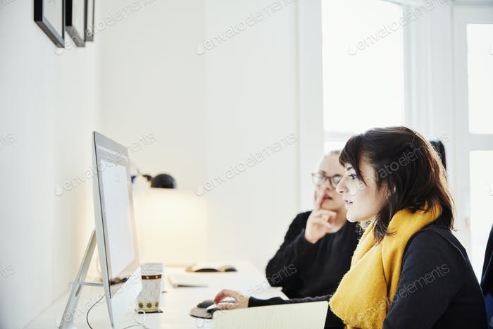 Two women seated sharing a computer screen and discussing the graphic content.