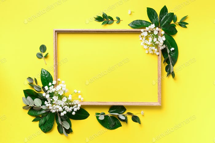 Creative layout with white flowers and copyspace over yellow background. Top view, flat lay. Spring