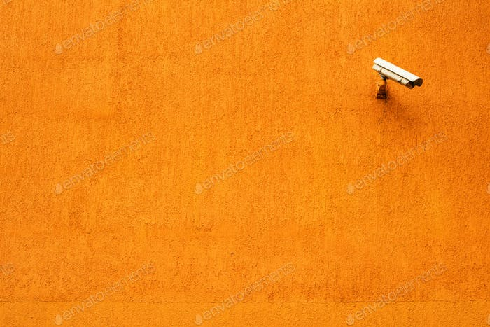 CCTV camera on orange building facade