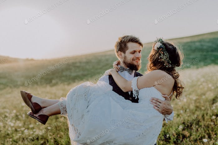 Beautiful bride and groom at sunset in green nature.
