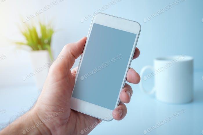 Mit Smartphone während der Kaffeepause am Morgen