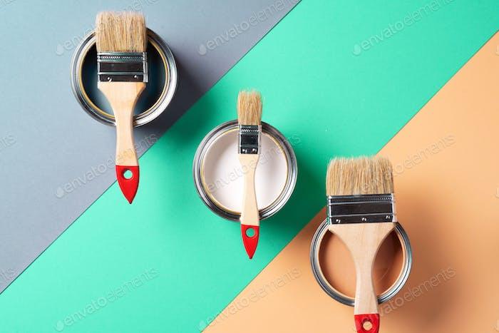 Metall-Farbdosen und Pinsel auf mehrfarbigen Hintergrund. Draufsicht. Kopierraum. Trendiges Grün