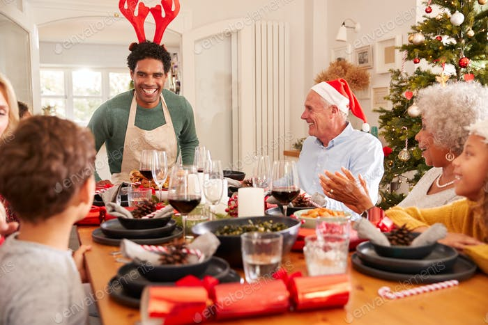 Multi-Generation Family Congratulating Father For Cooking Christmas Meal At Home