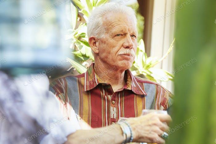 Старший мужчина с усами сидит на открытом воздухе.