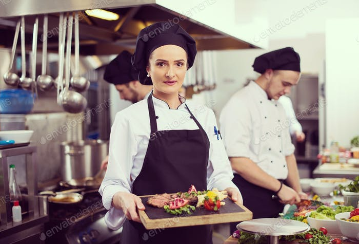 female Chef holding beef steak plate