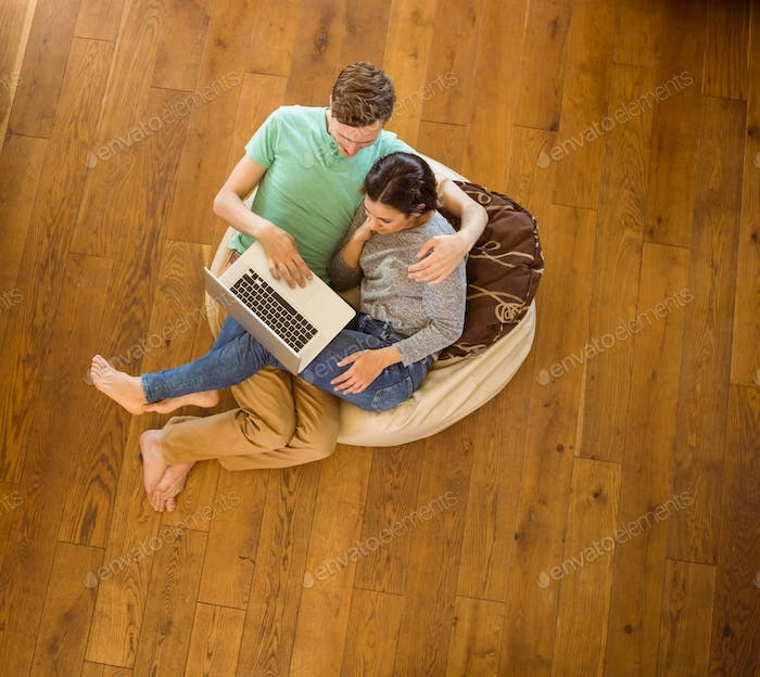 Cute couple using laptop on beanbag at home in the living room